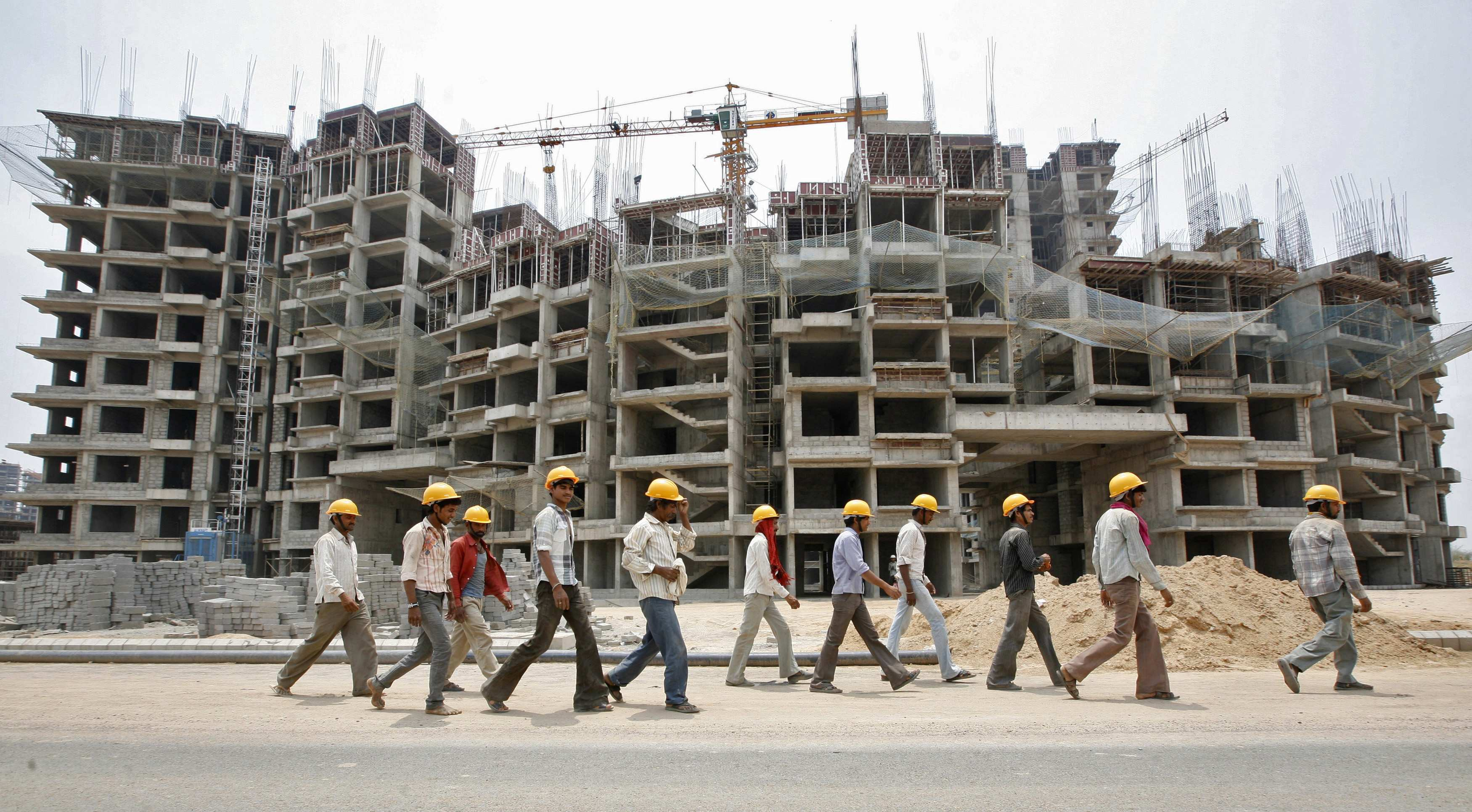 File picture shows workers walking in front of the construction site of a commercial complex on the outskirts of Ahmedabad
